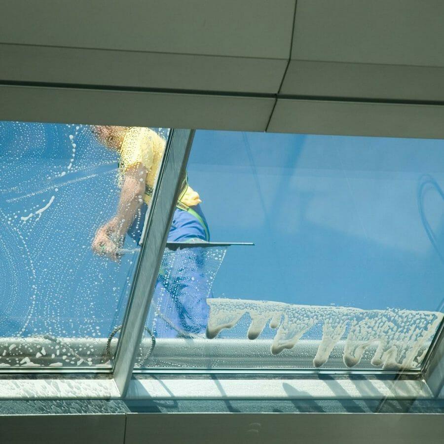 Glasreiniger reinigt Wintergarten mit Fenster